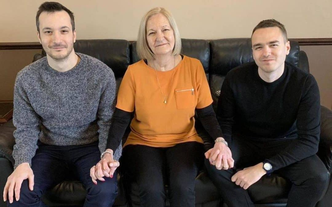 sally challen sitting on sofa with her two sons